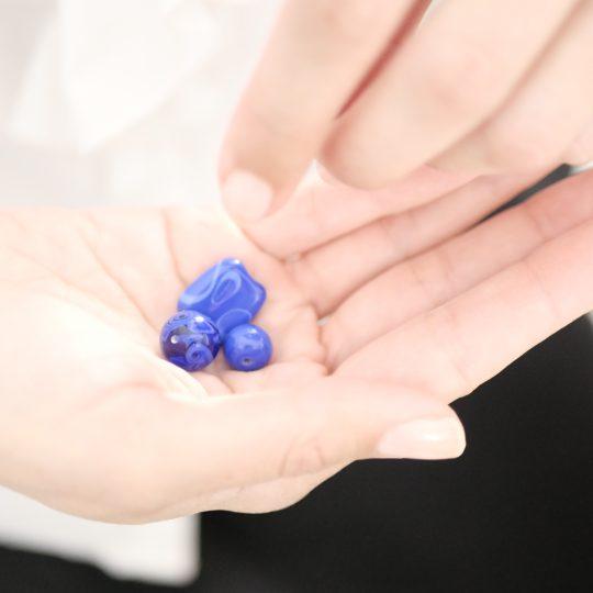 Mains avec des perles en verre de Murano bleu dans le creu de la main